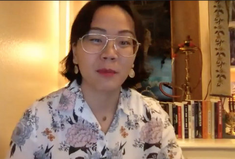 Asian woman wearing glasses with books behind her