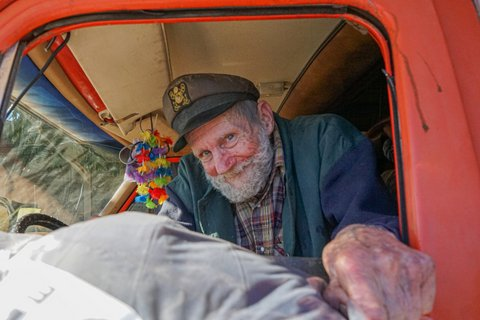 Man with gray beard and sea captain's cap receiving a bundle through the window of his car