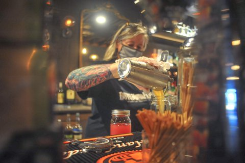 Woman with face mask and tattoo making cocktails.