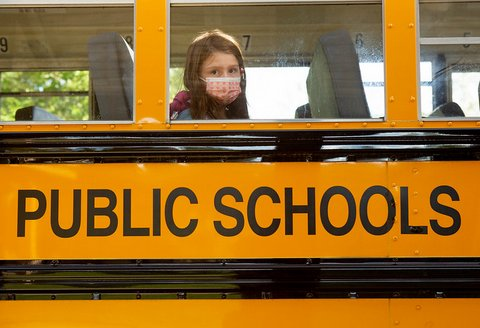 "Girl in face mask looks out the window of bus that says ""public schools"""