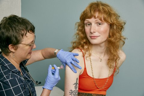 Red-haired woman getting vaccine shot in arm