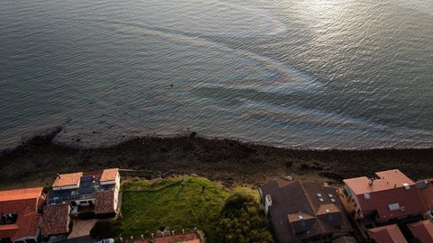 Overhead view of body of water with oil slick causing rainbow sheen