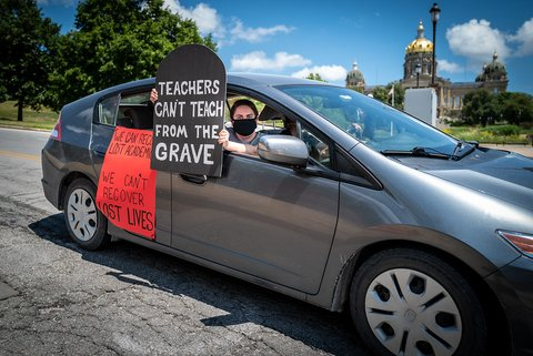 "Masked woman holding tombstone-shaped sign out car window that says ""Teachers can't teach from the grave."""