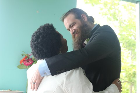A Black woman and white man standing with their arms around each other, looking into the other's eyes