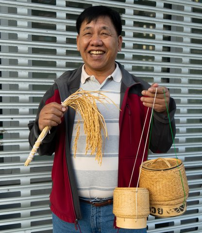 Smiling Asian man holding rice plant and Lao rice baskets.
