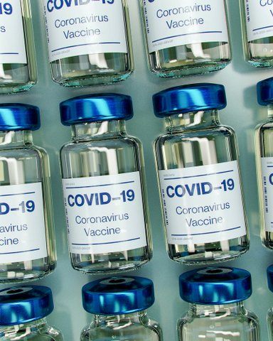 Small glass bottles with blue caps labeled COVID-19 coronavirus vaccine