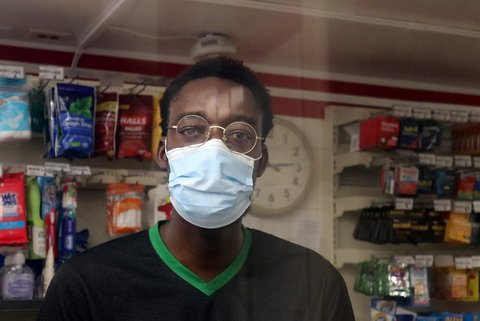 Black 7 Eleven worker wearing glasses and face mask