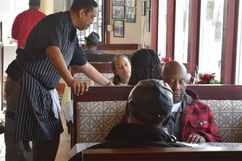Waiter and people in booths inside restaurant.