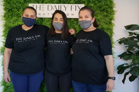 "Three Latinas in ""The Daily Fix Nutrition"" T-shirts in front of a plant wall with a Daily Fix sign."