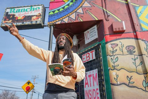 Donté Clark in front of Rancho Market, holding book with other arm outstretched.