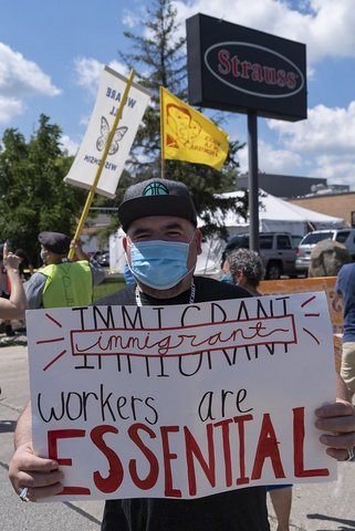 "Man in blue surgical mask holds sign that says ""Immigrant workers are essential."""