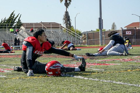 Players stretch on the field during a high school football practice.