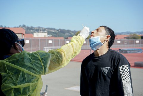 Medical worker swabs the nose of a young man with his mask pulled down.