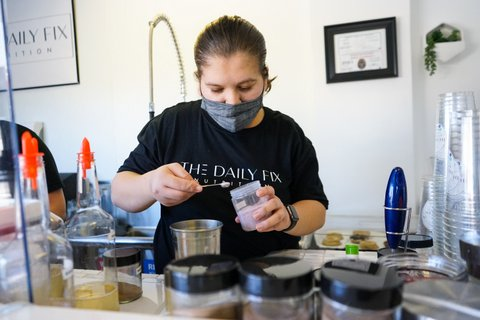 Woman in face mask and Daily Fix Nutrition T-shirt with hair pulled back scoops powder while preparing a drink.