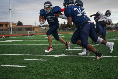 Football player runs with ball held to his side