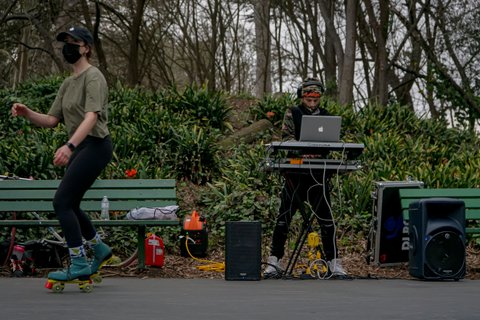 DJ between park benches with trees in background and skater in a mask in the foreground.