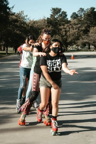 A line of roller skaters each with their hands on the shoulders of the person in front of them.