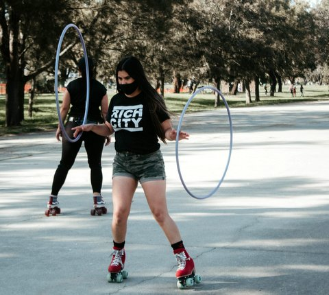 Woman in black Rich City T-shirt and red skates with a hula hoop balanced on each hand.