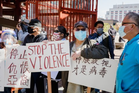 """Asian people in masks with one sign that says """"stop the violence"""" and two other signs in Chinese script."""