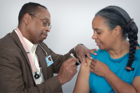 Black man gives vaccine shot in Black woman's arm