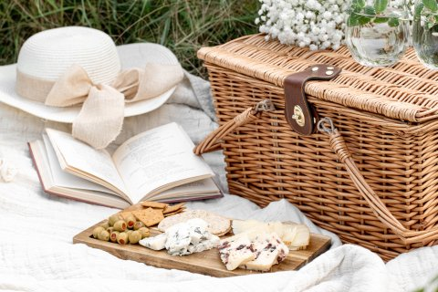 Picnic basket, hat, open book and cheeseboard on a blanket.