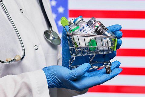 Closeup of vials in tiny shopping cart held by person with lab coat, stethoscope and blue-gloved hands against U.S. flag background