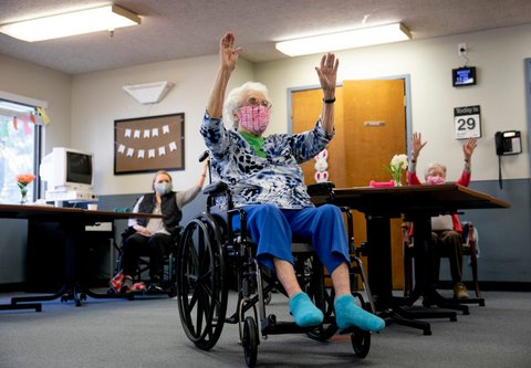 White-haired woman in wheelchair with arms raised
