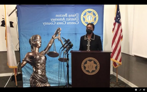 Black woman at lectern with U.S. flag and picture of Lady Justice behind her.