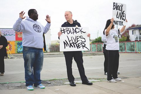 White police officer holding Black Lives Matter sign and looking at Black man