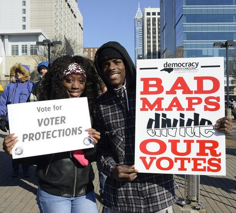 "Black woman with sign that says ""Vote for voter protections"" and Black man with sign that says ""Bad maps divide out votes."""