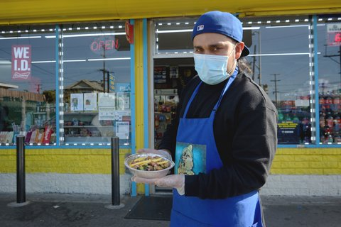 Man wearing face mask, gloves and blue apron and backwards baseball cap holds a dish of food outside a market.