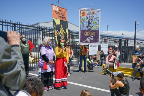 """A young woman in a mask, yellow top and red skirt speaks into a microphone among a crowd of people. Signs nearby read """"no new fossil fuel projects"""" and """"keep it in the ground."""""""