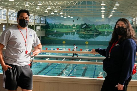 A young Latino man and woman, both wearing masks, standing a few feet apart with a railing behind them and pool below.