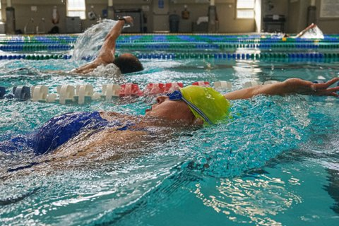 Woman in blue bathing suit, goggles and yellow-green swim cap doing the backstroke