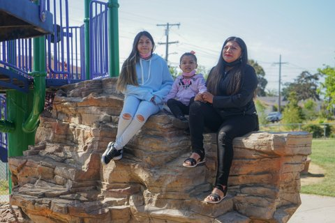 A 12-year-old girl, a 4-year-old girl and their mother sitting left to right on rocks in a park.