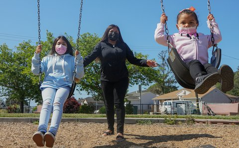 Latina woman pushing her two daughters on swings
