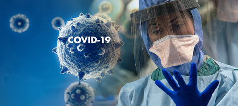 Image of coronavirus cells, one with the words COVID-19 on it, next to a medical worker in full protective gear looking at her gloved hand.