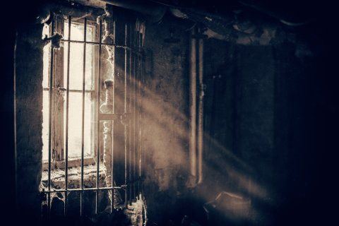 Grayscale photo of sunlight streaming through barred window