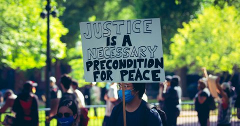 """Person in mask and glasses holding sign that reads """"Justice is a necessary condition for peace"""""""