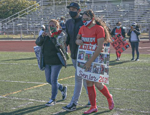 Girl in red soccer uniform and white mask holding sign and walking on field with two people