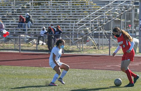 Girls soccer player with the ball and opponent nearby