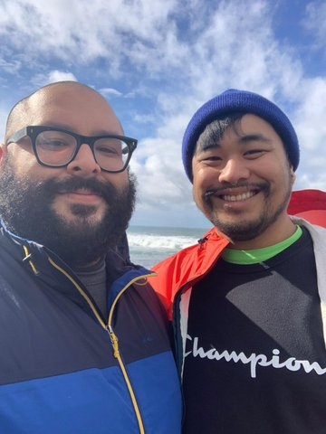 Two smiling young men standing side by side against a blue sky
