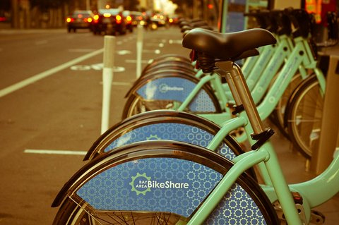 A row of light green Bay Area Bikeshare bicycles