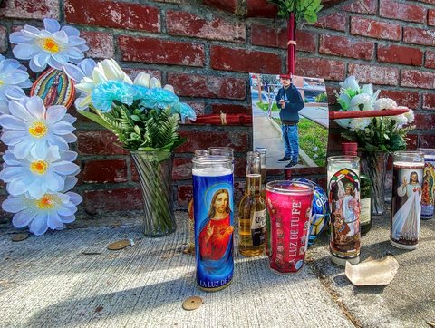Memorial in front of a brick wall with religious candles, flowers and a photo of a young man