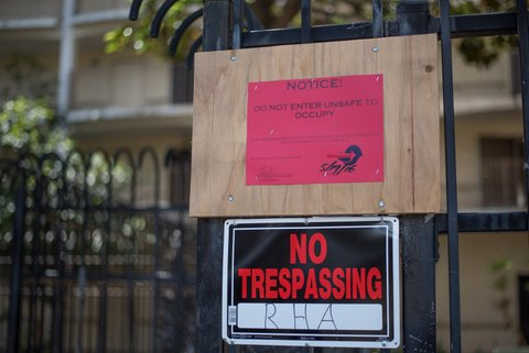"""Two signs on a fence. One says """"Notice! Do not enter unsafe to occupy."""" The other says """"No trespassing RHA."""""""