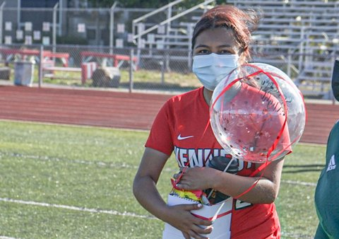Young woman in white mask and red Kennedy T-shirt holding clear balloon