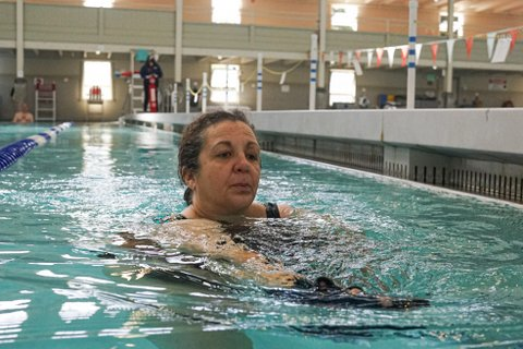 Older woman standing in a swimming pool
