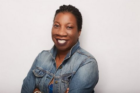 A smiling Black woman with short hair and a denim jacket