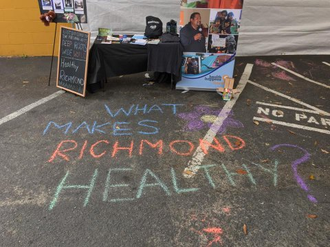 """Chalk writing that says """"What makes Richmond healthy?"""" on asphalt in front of a booth"""