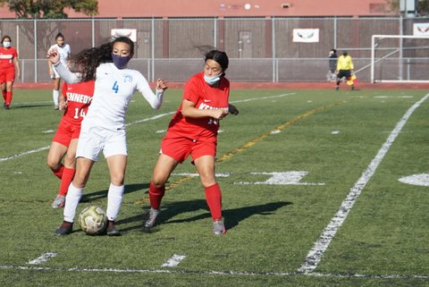 Two girls soccer players going for the ball. Both have masks. One is in red and one is in white.